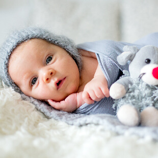 Baby laying down, looking curiously into camera with blankets and stuffed animals