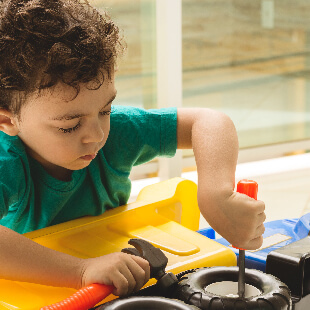 Child playing with toy truck as if he is repairing it with toy tools